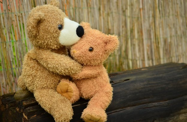 Two teddy bears hugging